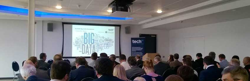 An audience in lecture-style seating watching a presentation at the TechUK Big Data In Action Roadshow.
